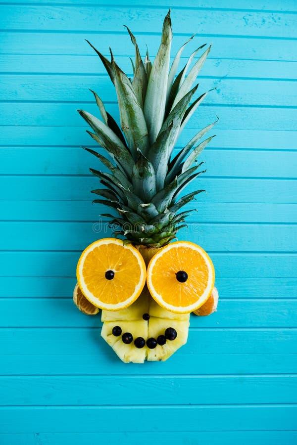 Applique drôle des morceaux de fruit sur un fond en bois de turquoise Tête de fruit faite d'ananas, orange, verticale photographie stock libre de droits