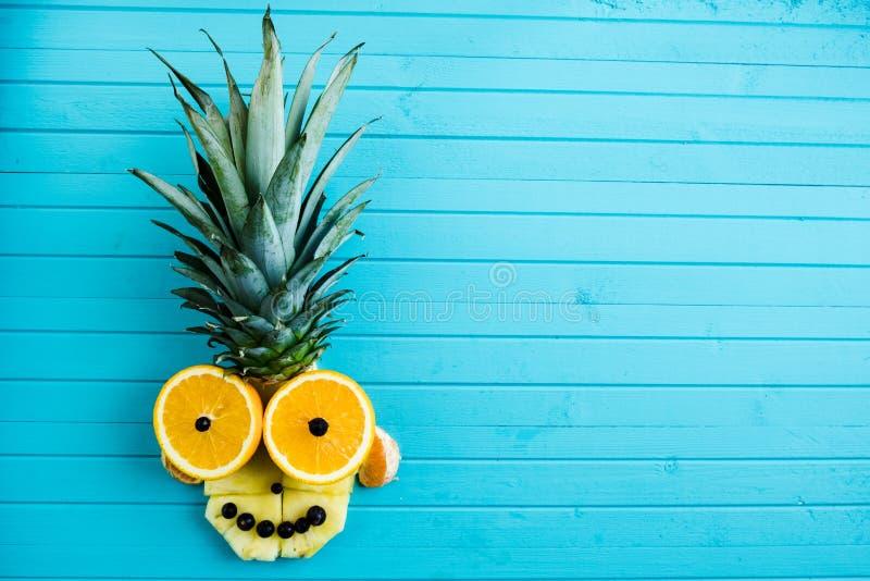 Applique engraçado das partes de fruto em um fundo de madeira azul Cabeça do fruto feita do abacaxi, laranja, espaço da cópia fotos de stock