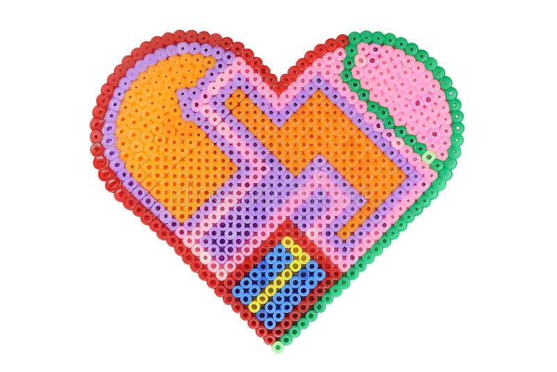Applique na forma de um coração feito dos grânulos coloridos plásticos brilhantes isolados no branco fotografia de stock royalty free