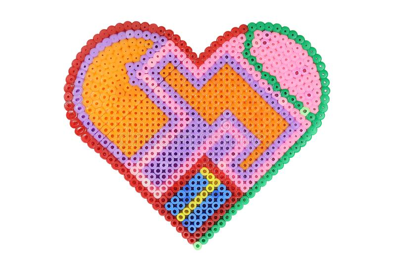 Applique in the shape of a heart made of shiny plastic multicolored beads isolated on white royalty free stock photography