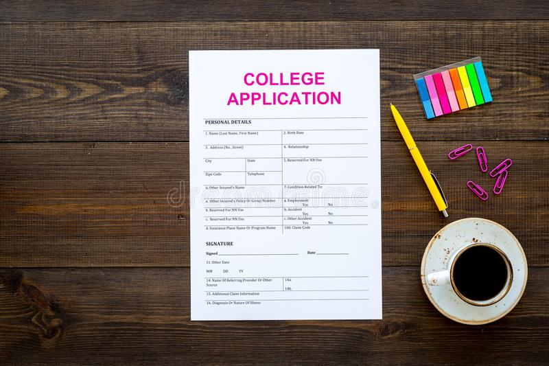 Apply college. Empty college application form near coffee cup and stationery on dark wooden background top view copy royalty free stock photo