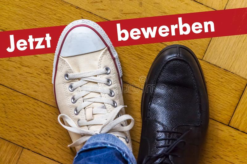 Apply Now Concept in German. An elegant business shoe and a casual shoe with the Phrase Apply Now in German stock photo