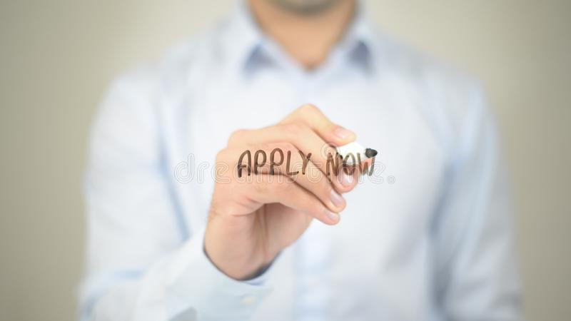 Apply Now, Man writing on transparent screen royalty free stock photo