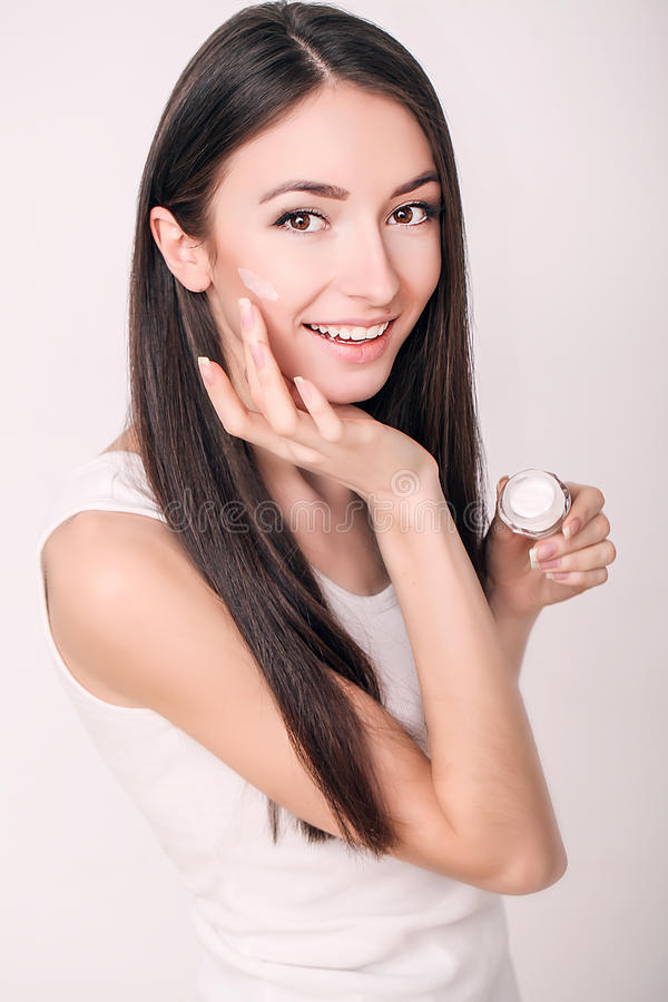Applying cosmetic cream. A beautiful young woman applying face moisturizer. Scine care of the face and hands.  stock photos