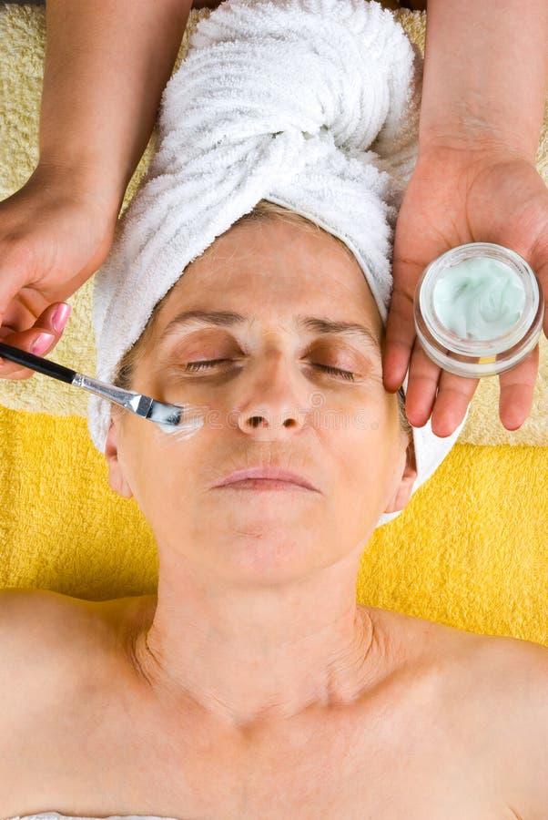 Applying cream mask on senior face stock image