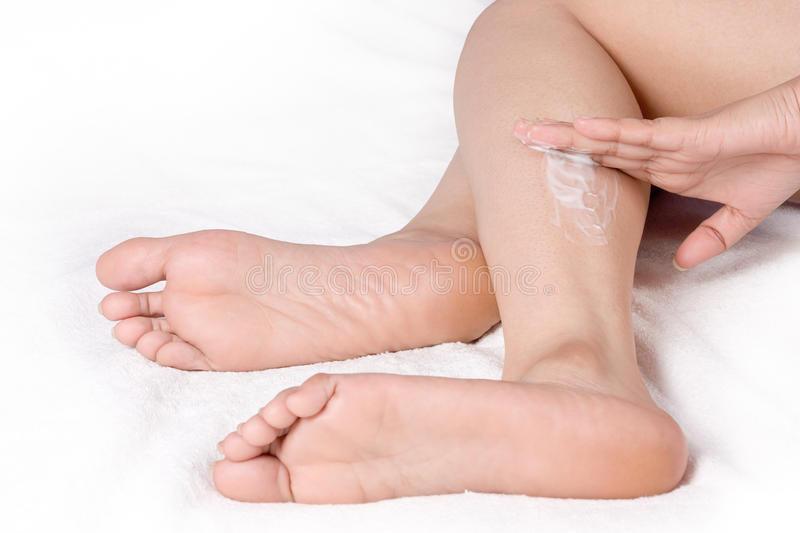 Applying cream to leg stock images