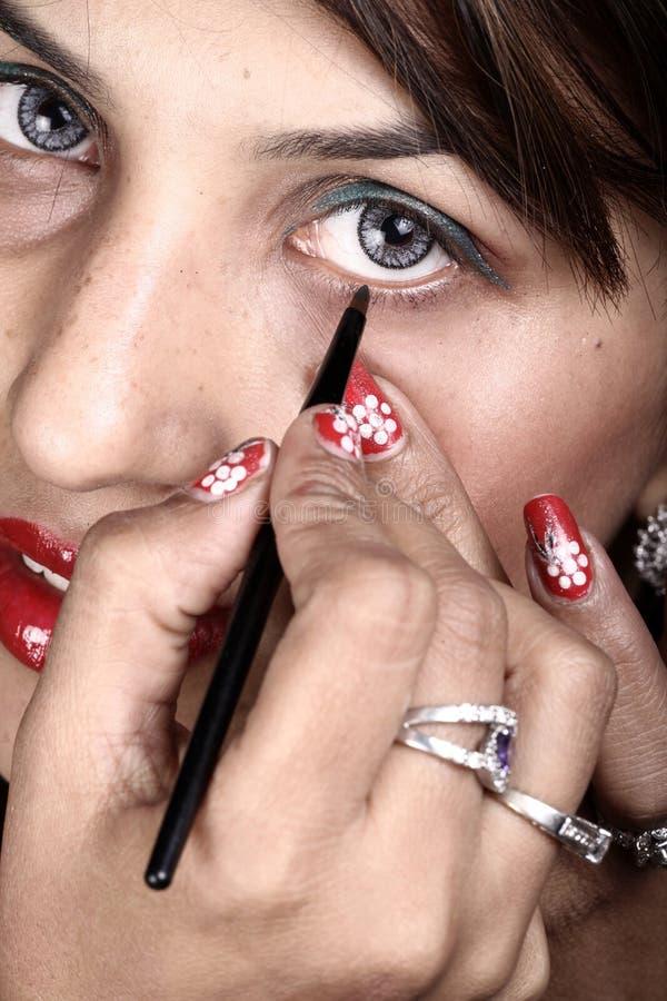 Applying eye liner royalty free stock photos