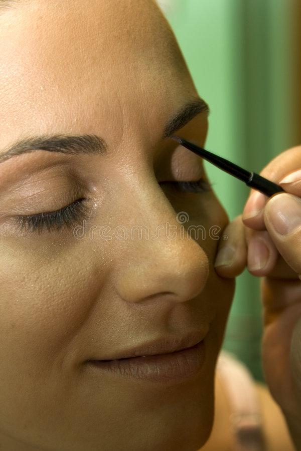 Applying Eyebrow Pencil. Close up of beautician creating makeup for a young women in the beauty parlour stock images