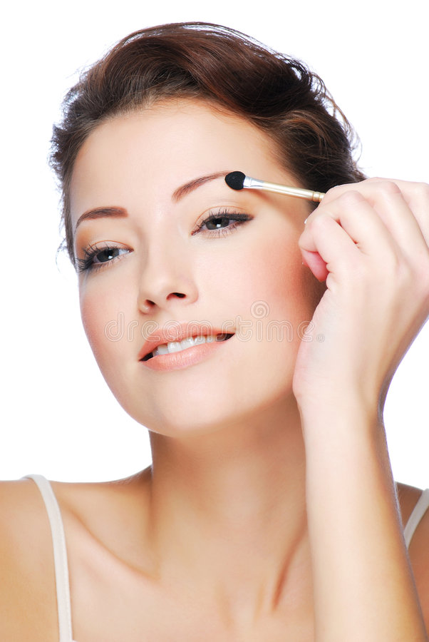 Applying eyeshadow using cosmetic applicator. Portrait of beauty young caucasian woman applying eyeshadow using cosmetic applicator stock photos