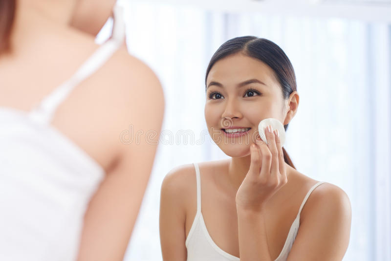 Applying face toner. Smiling young woman applying toner on her face in front of mirror royalty free stock photography