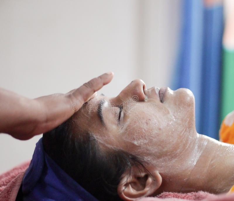 Applying facial pack mask cream on face of a lady with hair band with eyes closed.side view.  royalty free stock image