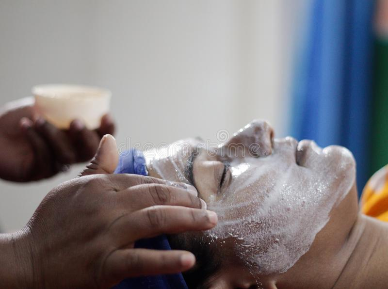 Applying facial pack mask on face of a lady with hair band with eyes closed.side view.  royalty free stock image