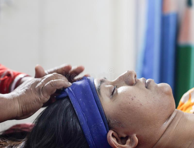 Applying facial pack mask gel on face of a lady with hair band with eyes closed.side view.  royalty free stock photo