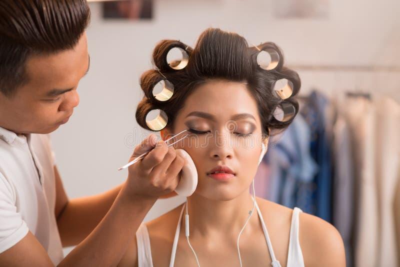 Applying falsies. Make-up artist applying false eye lashes on beautiful young woman royalty free stock photo