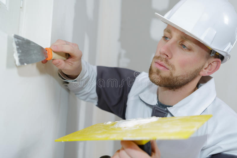 Applying finishing touch on wall royalty free stock images