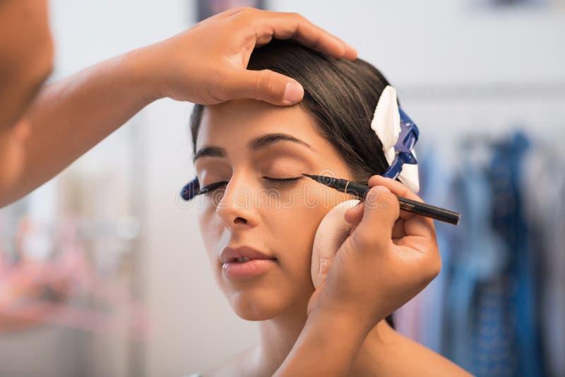Applying gel liner. Make-up artist applying black gel eyeliner on beautiful woman royalty free stock photo