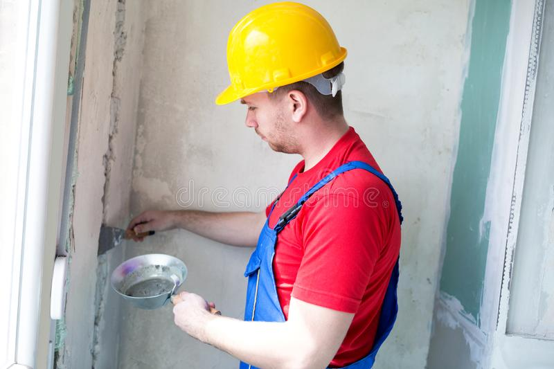 Applying gypsum mixture on a wall hollows stock photography
