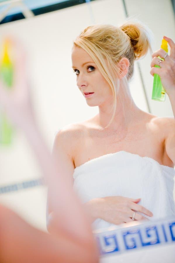 Applying Hairspray stock photo