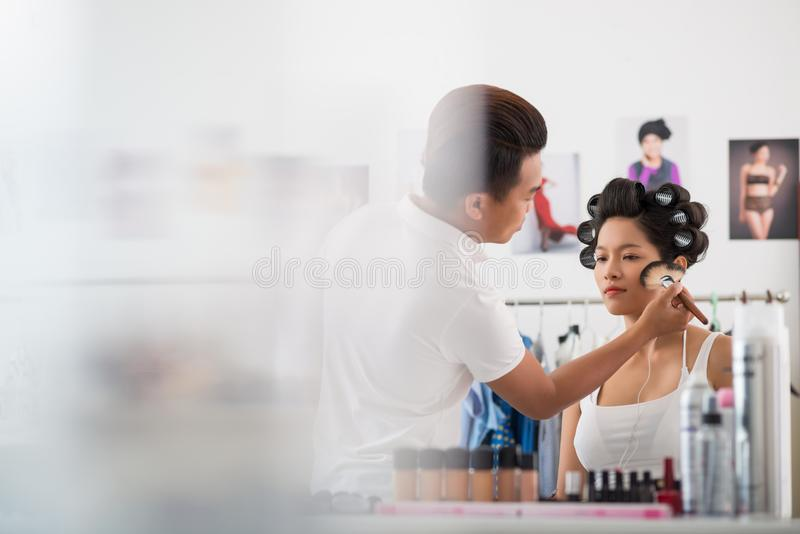 Applying highlighter. Make-up artist applying highlighter to the cheeks of you Asian model royalty free stock photography