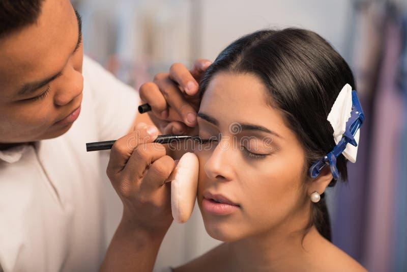 Applying liner. Make-up artist drawing perfect eyeliner on beautiful model stock image