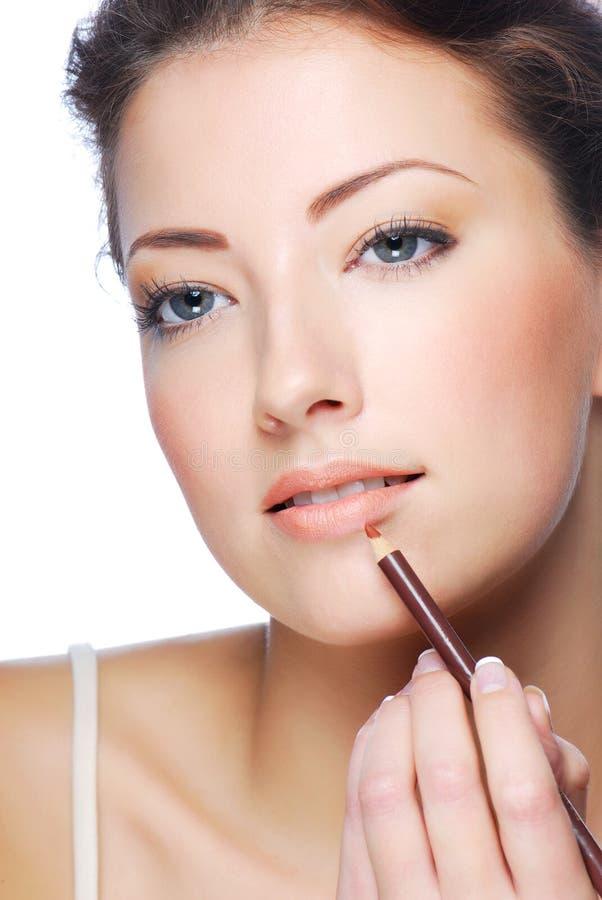 Applying lipstick using lip concealer brush. Portrait of beautiful woman applying lipstick using lip concealer brush stock photos