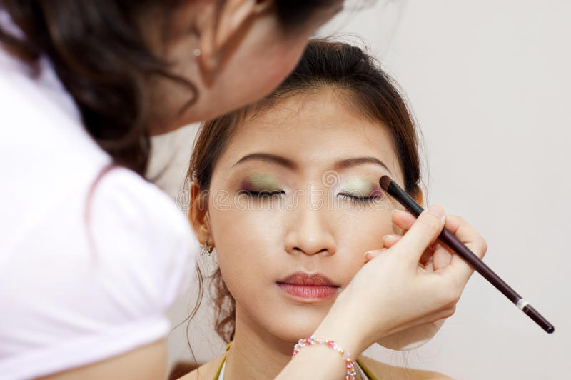 Applying makeup. Woman applying cosmetic with applicator. Make-up treatment royalty free stock photos