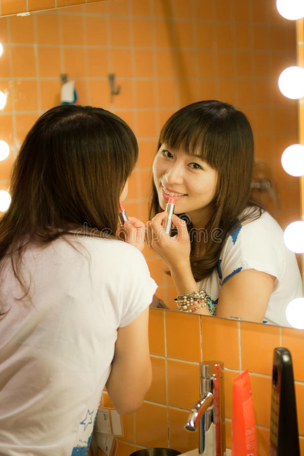 Applying makeup. Close-up of gorgeous female applying bright makeup royalty free stock photo