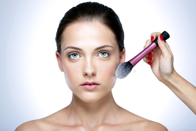 Applying makeup on the face with a large brush stock photo