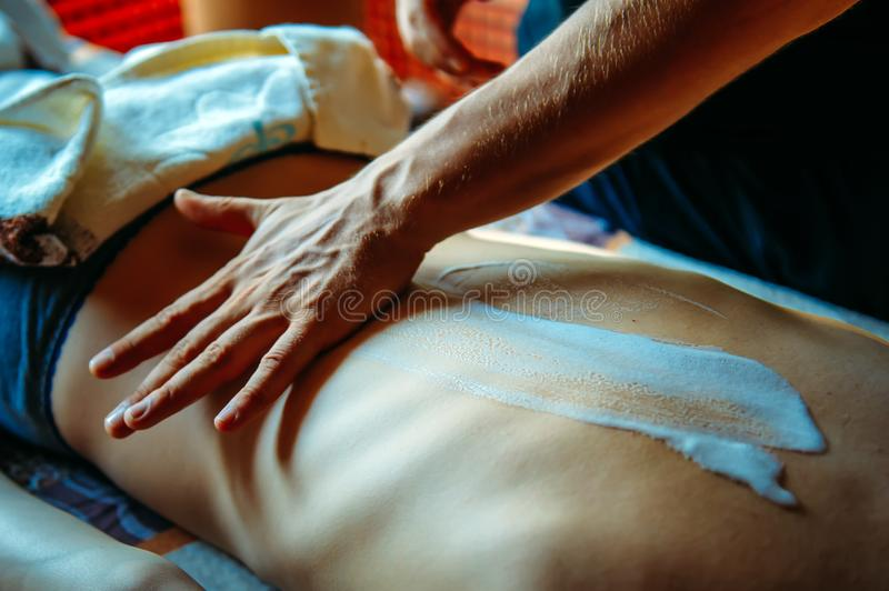 Applying moisturizing cream on the female back before massage - close-up. People, beauty, healthy lifestyle and relaxation concept royalty free stock photography