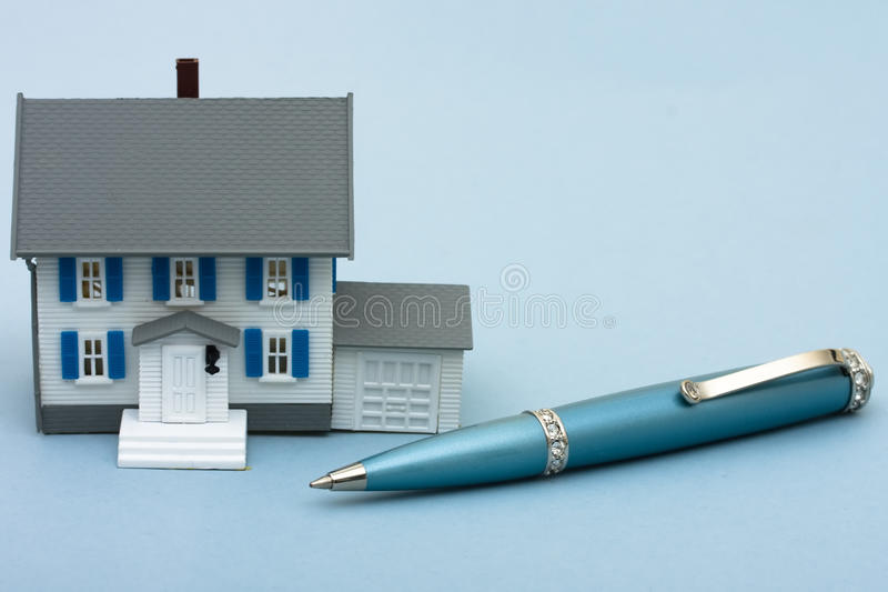 Applying for a Mortgage. A blue pen with a model house sitting on a blue background, applying for a mortgage royalty free stock images