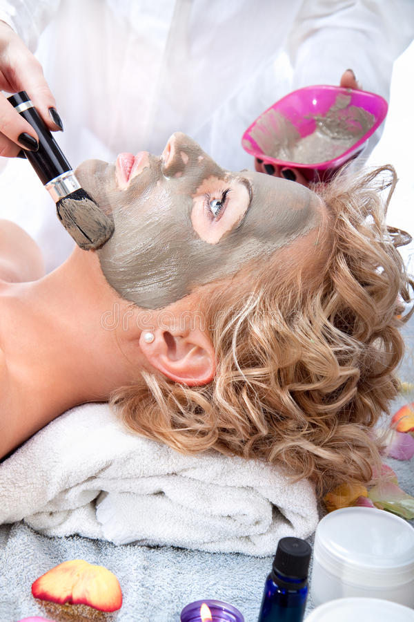 Applying mud face pack on woman face stock images