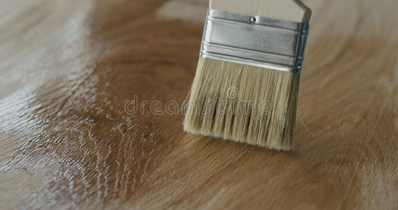 Applying oil finish to oak surface with brush. Wide photo stock images