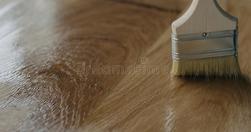 Applying oil finish to oak surface with brush. Wide photo stock photos