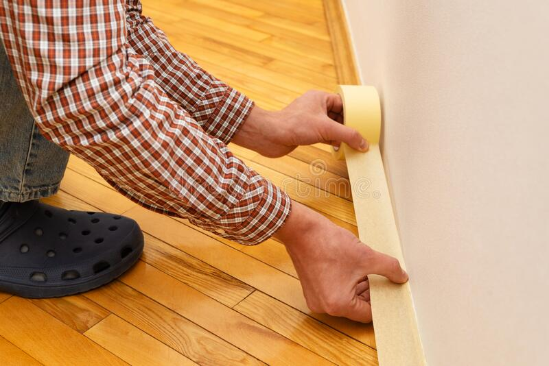 Applying paint tape to the baseboard stock photo
