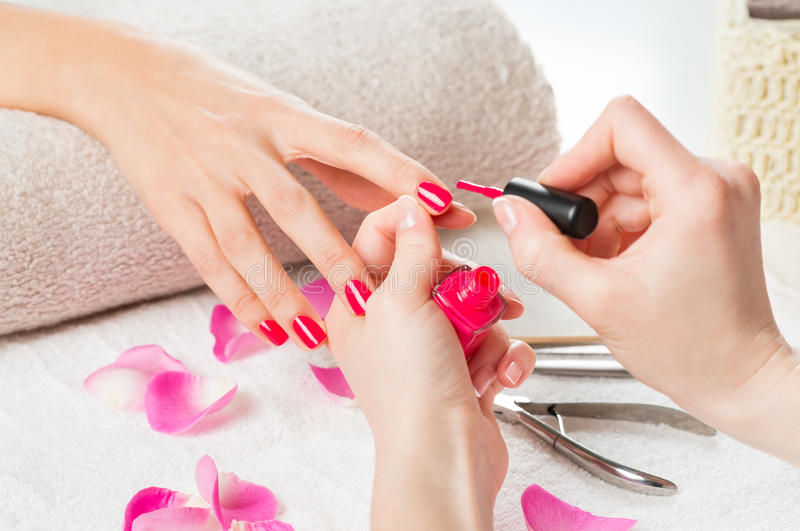 Applying pink nail polish. Closeup shot of a beautician applying nail polish to female nail in a nail salon. Close up of a women hand with pink nailpolish after royalty free stock photography