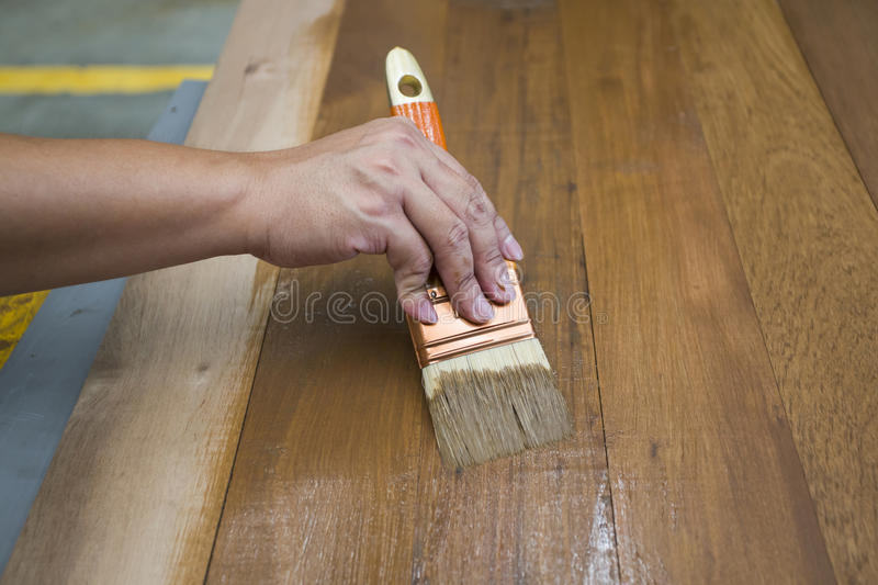 Applying protective varnish on a wooden furniture. Wood working royalty free stock photography