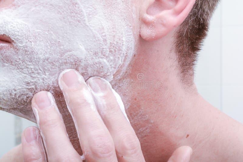 Applying shaving foam. To face before shaving in the bathroom stock image