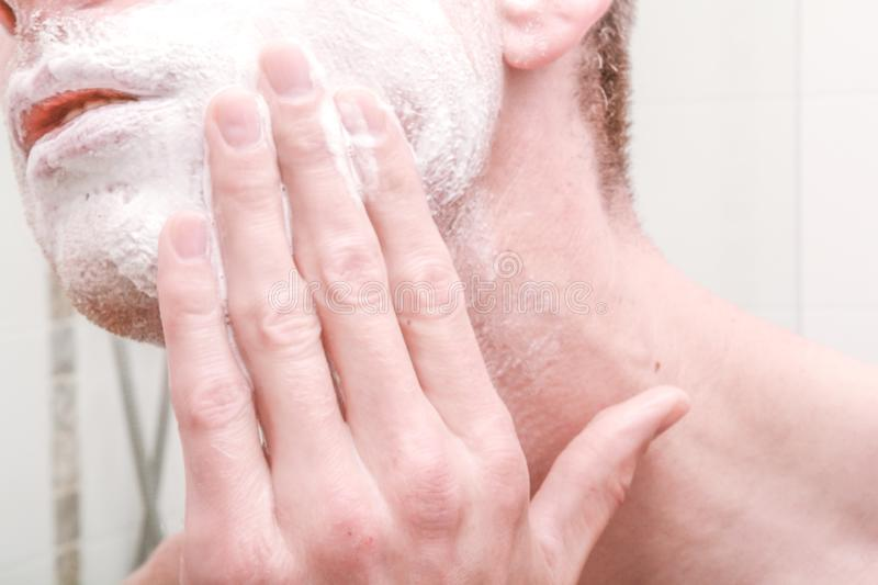 Applying shaving foam. To face before shaving in the bathroom royalty free stock images