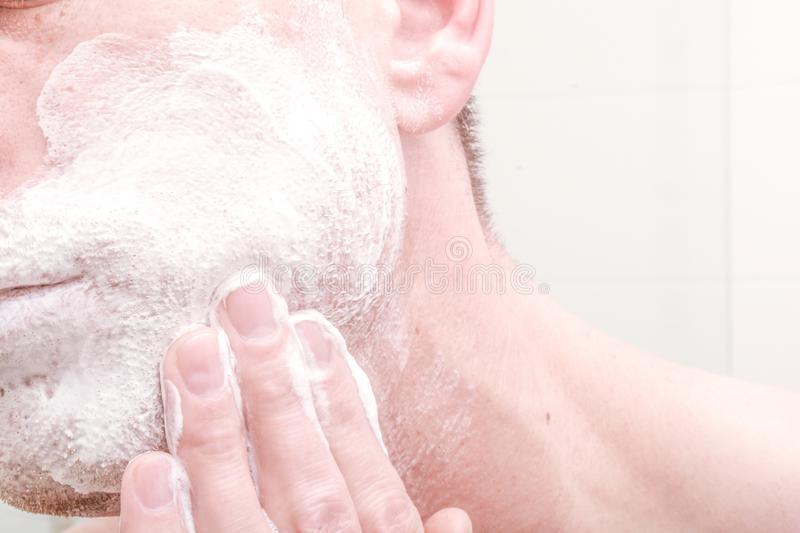 Applying shaving foam. To face before shaving in the bathroom royalty free stock photography