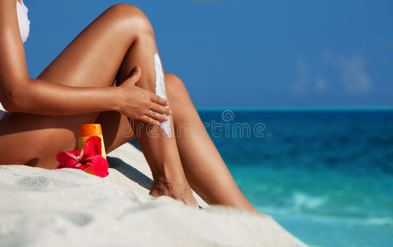 Applying sunscreen on the skin. Woman sitting on the beach and moisturizing her skin royalty free stock image