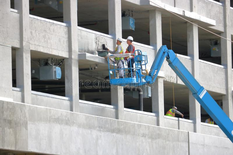 Applying Tar Sealant to Concrete Wall. A construction supervisor watches as a crew member applies tar sealant to a cement wall in Richmond, British Columbia stock photography