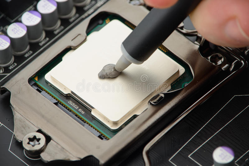 Applying thermal paste to CPU. Applying thermal paste to processor on motherboard stock photos