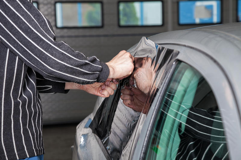 Applying tinting foil on a car window stock image