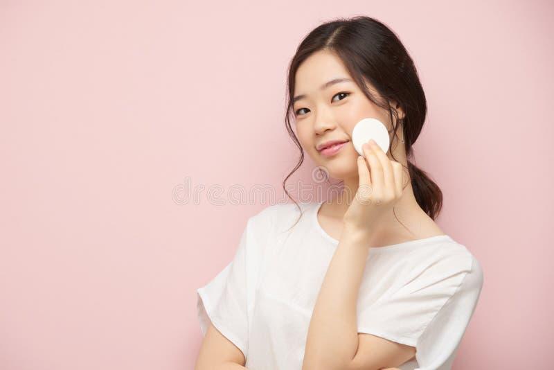 Applying toner. Lovely Korean woman applying toner on her skin stock photography