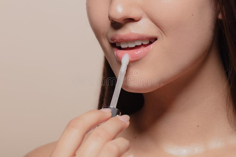 Applying transparent lip gloss. Close up of young korean woman applying transparent lip gloss. Cropped shot of girl putting on makeup on her lips with applicator stock image