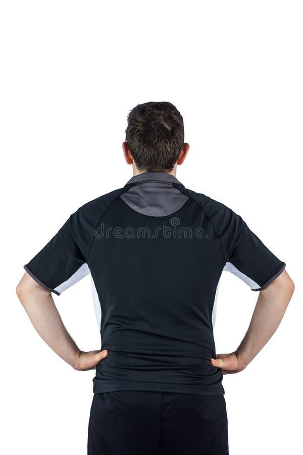 Appoggi il giocatore girato di rugby con le mani sulle anche immagine stock