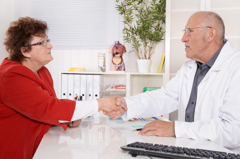 Appointment at doctor: older woman talking with a specialist. Appointment at doctor: older women talking with a specialist sitting at desk stock photo