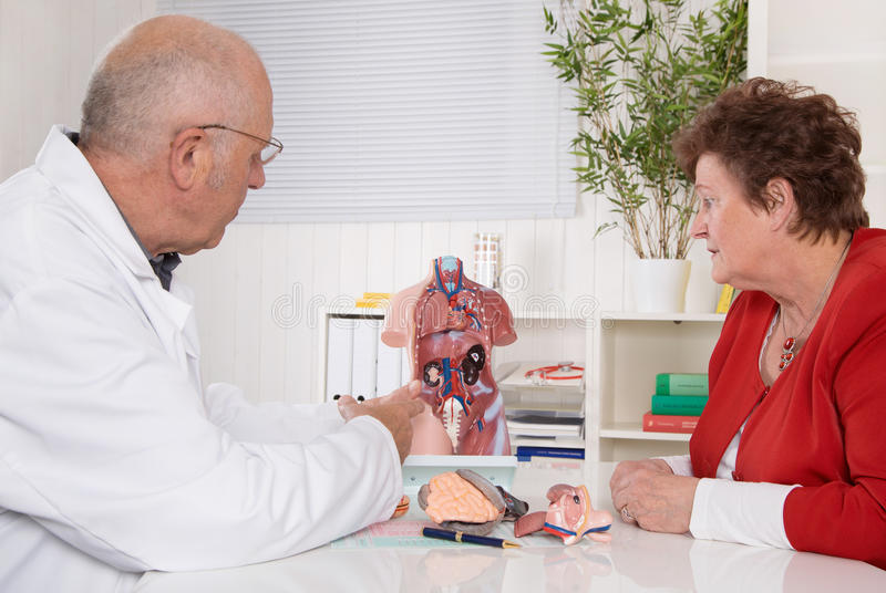 Appointment: senior patient and older male doctor. Senior doctor with an older women explaining the human body royalty free stock photo