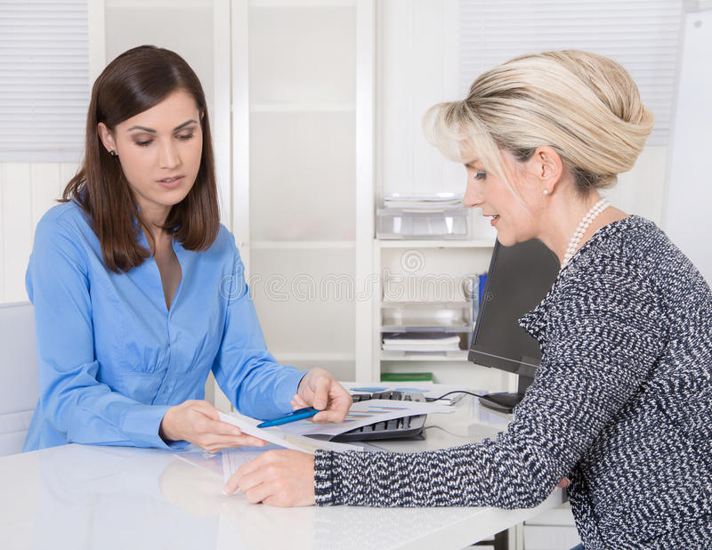 Appointment at a specialist for finance: female customer and adv. Iser sitting at desk talking about a contract or business solutions.Concept teamwork or job royalty free stock images