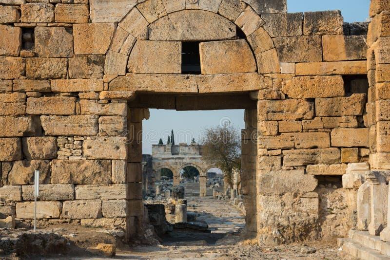 Appollo寺庙废墟有堡垒的后面的在古老科林斯湾,伯罗奔尼撒,希腊 免版税库存照片